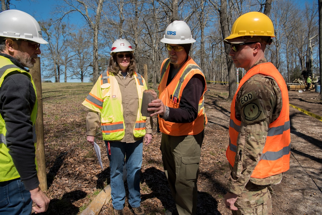 Don Coberley, URS-AECOM field project manager, shows a ground sample to U.S. Air Force Maj. Brandon Goebel, 20th CES commander, at Sans Souci Farm in Sumter, S.C., March 7, 2019.
