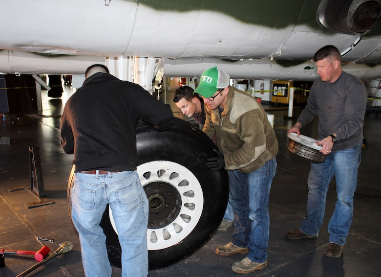 Master Sgt. Ron Williams holds the outer brake assembly of a B-25 at Patriots Point Martime Museum in Mount Pleasant, S.C., as Tech. Sgt. Nathon Andrews (background), Staff Sgt. Mark Jacobs (right) and Airman 1st Class Christopher Garren (left) slowly remove the wheel and tire assembly from the axle.