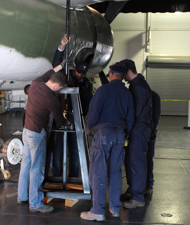 Tech. Sgt. Nathon Andrews (center) and members from Patriots Point maintenance staff, place a tripod jack under the wing of a B-25 bomber located at Patriots Point Maritime Museum in Mount Pleasant, S.C., to facilitate removing the wheel and tire assembly.