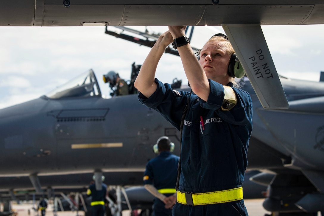 An airman uses a tool to work on a jet with another jet in the background.