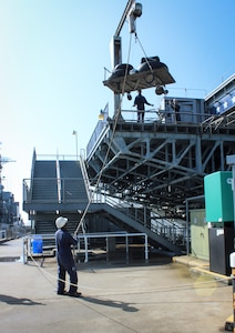 Members of Patriots Point's maintenance staff use a crane to bring the two main landing gear and nose gear wheel and tire assemblies up to the main deck of the USS Yorktown, where the B-25 is located at the Patriots Point Maritme Museum in Mount Pleasant, S.C.