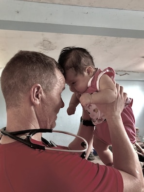 Lt. Col Christopher Wilhelm, 22nd Medical Group chief medical officer, holds a baby at a clinic in San Martin Region, Peru, March 2019. During the mission, the medical team saw 826 patients throughout seven towns that did not have access to consistent medical care. (Courtesy Photo)