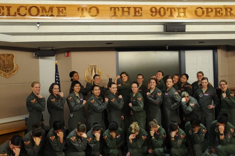 """Missileers of the 90th Missile Wing  strike their """"Rosie the Riveter"""" pose for a  photo March 7, 2019, on F.E. Warren Air Force Base, Wyo. The 90th Missile Wing participated in an all-female alert during Women's History Month. For 24 hours, female crews operated all ICBM silos across the United States. (U.S. Air Force photo by 2nd Lt. Jonathan Carkhuff)"""
