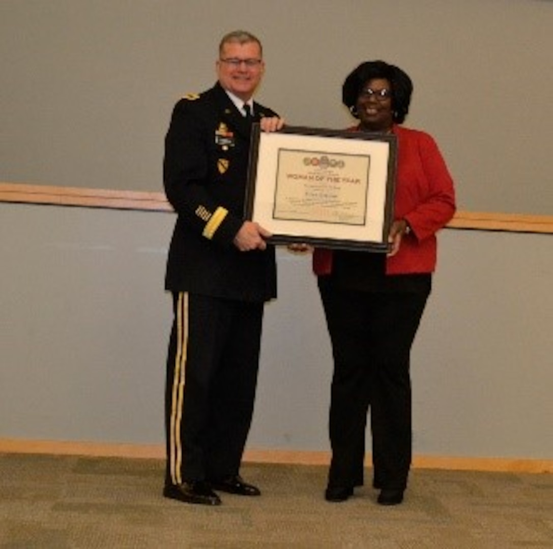 Army Brig. Gen. Mark Simerly, DLA Troop Support commander, left, presents Robin Whaley, right, Subsistence supply chain supervisor, a plaque on behalf of Gina Breleur, a Troop Support Europe and Africa employee, for her exemplary model of public service and government leadership during the Women's History Month Program March 13. Breleur was selected Woman of the Year in the non-supervisory GS-9 and below category. (Photo by Alexandria Brimage-Gray)