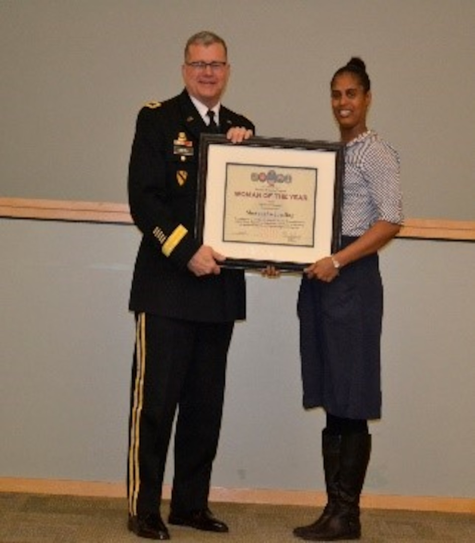 Army Brig. Gen. Mark Simerly, DLA Troop Support commander, left, presents Shevaughn Jorsling, right, Construction and Equipment supply chain supervisor, a plaque for her exemplary model of public service and government leadership during the Women's History Month Program March 13. Jorsling was selected Woman of the Year in the supervisor/manager of the year category.  (Photo by Alexandria Brimage-Gray)