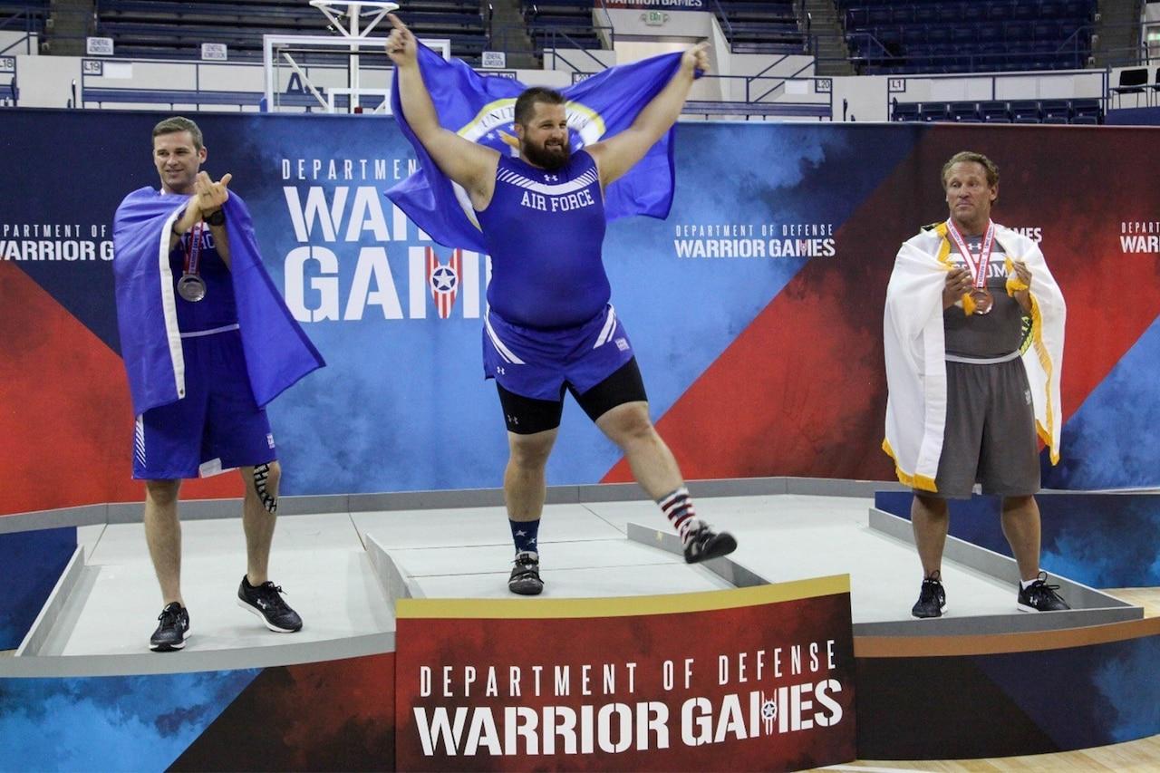 Athletes stand on platform.
