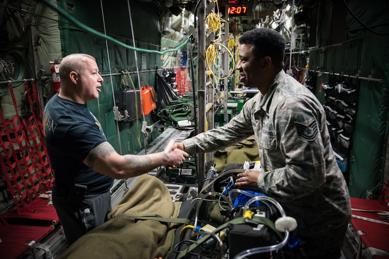 Marine Corps Staff Sgt. (Ret.) Daniel Gilyeat, who lost his left leg in an explosion in July 2005 when his Up Armored Humvee ran over a double-stacked anti-tank mine in Iraq, greets Tech. Sgt. Donald Ennis Jr., NCOIC of the Aeromedical Evacuation Course at the United States Air Force School of Aerospace Medicine. Ennis provided a coin to Gilyeat on behalf of the En Route Care Training Department as they toured one of the C-130 trainers in USAFSAM's High Bay. Gilyeat was visiting USAFSAM to speak to students at the Aerospace Medicine Primary course March 4. (U.S. Air Force photo/Richard Eldridge)