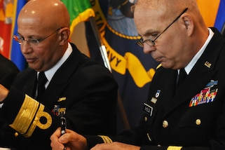 Chief of International Affairs at the Brazil Ministry of Defense, Rear Admiral Guilherme Da Silva Costa (left) and New York National Guard Adjutant Gen., Maj. Gen. Raymond Shield (right), sign a state partnership agreement, on the U.S.S. Intrepid, Manhattan, N.Y., March 14, 2019.