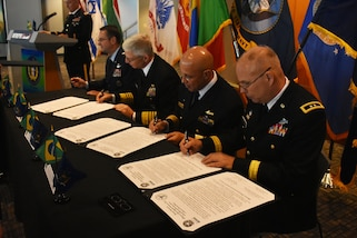 Chief of International Affairs at the Brazil Ministry of Defense, Rear Admiral Guilherme Da Silva Costa(center right) and New York National Guard Adjutant Gen., Maj. Gen. Raymond Shields (right), sign a state partnership agreement, on the U.S.S. Intrepid, Manhattan, N.Y., March 14, 2019.
