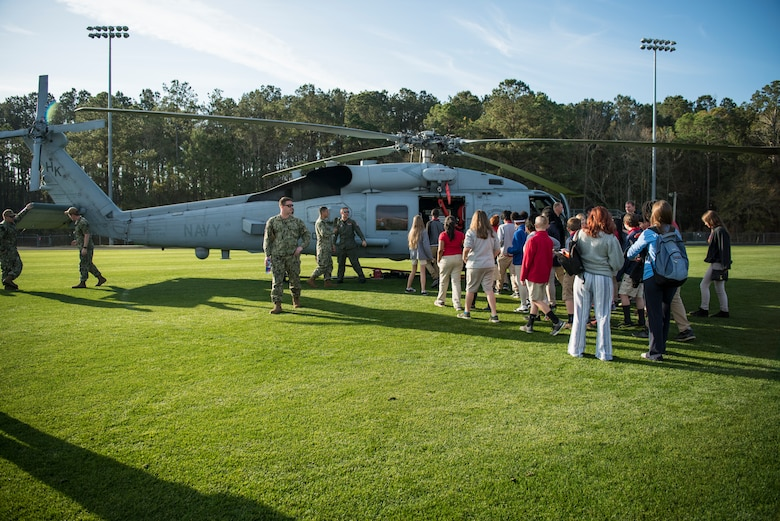 Students gather around the Helicopter Maritime Strike Squadron Four-Zero during a Navy Week school visit March 14, 2019, on John's Island, S.C.