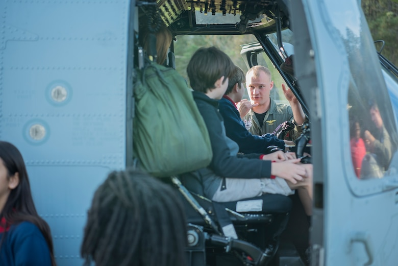 Lt. Justin Norris, a Helicopter Maritime Strike Squadron Four-Zero fleet replacement instructor pilot, talks to students about the helicopter during a Navy Week school visit March 14, 2019, in John's Island, S.C.
