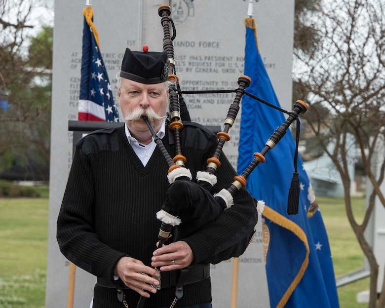 bagpiper playing song with flags behind them