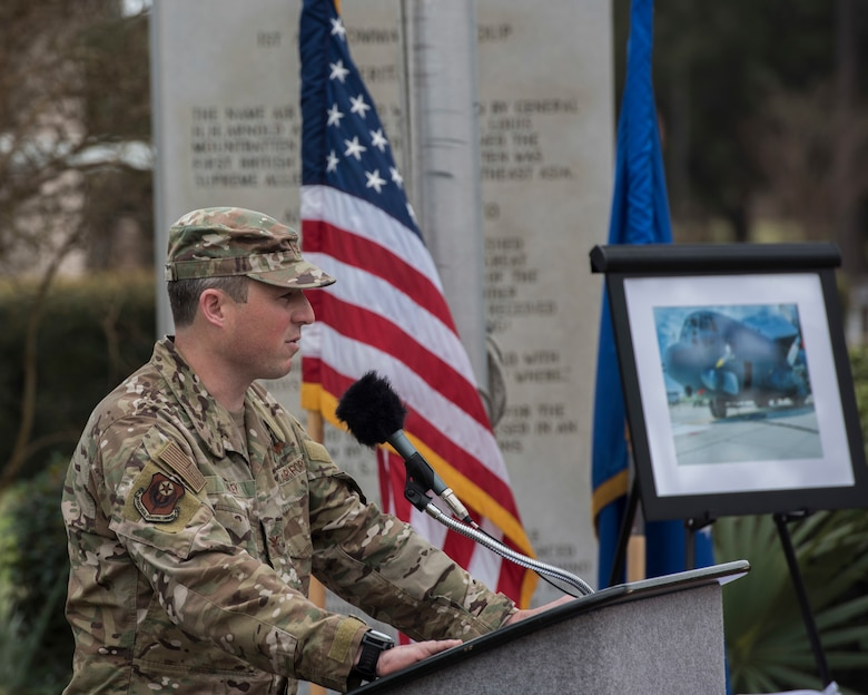 Colonel speaking at a podium outside.