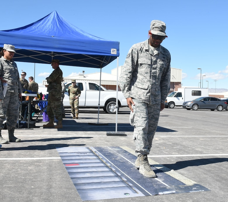 Staff Sgt. Kevin, 432nd Wing Chapel chaplain's assistant, attempts to walk a straight line while wearing alcohol-impairment-simulating goggles during the second annual anti-drug town hall and DUI awareness course at Creech Air Force Base, Nevada, March 7, 2019. Base representatives converged to educate Creech Airmen about updated U.S. Air Force drug policies, and the dangers of driving while impaired. (U.S. Air Force photo by Tech. Sgt. Dillon White)
