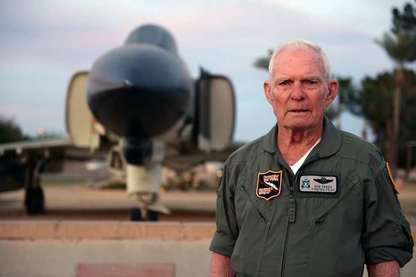 A veteran stands in front of an aircraft on display.
