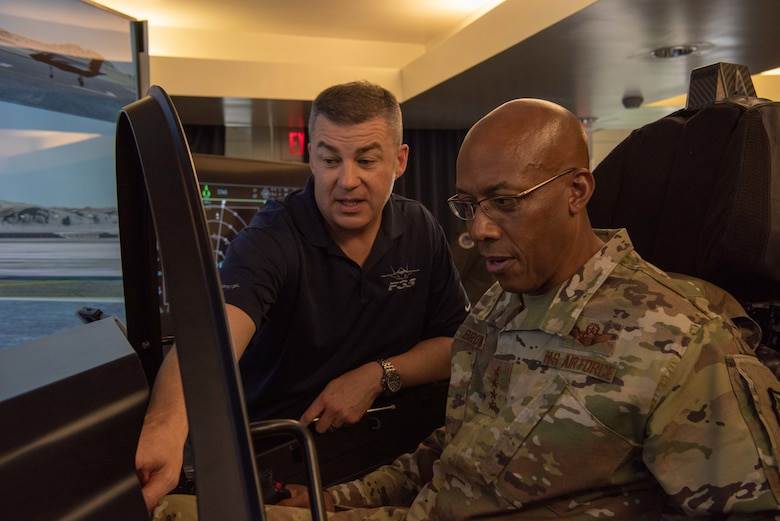 Adrean Clark, Lockheed Martin Operations analyst, demonstrates how to read the displays in the F-35 simulator to U.S. Air Force Gen. CQ Brown, Jr., Pacific Air Forces commander, during the Pacific F-35 Users Group Conference at Joint Base Pearl Harbor-Hickam, Hawaii, March 12, 2019.