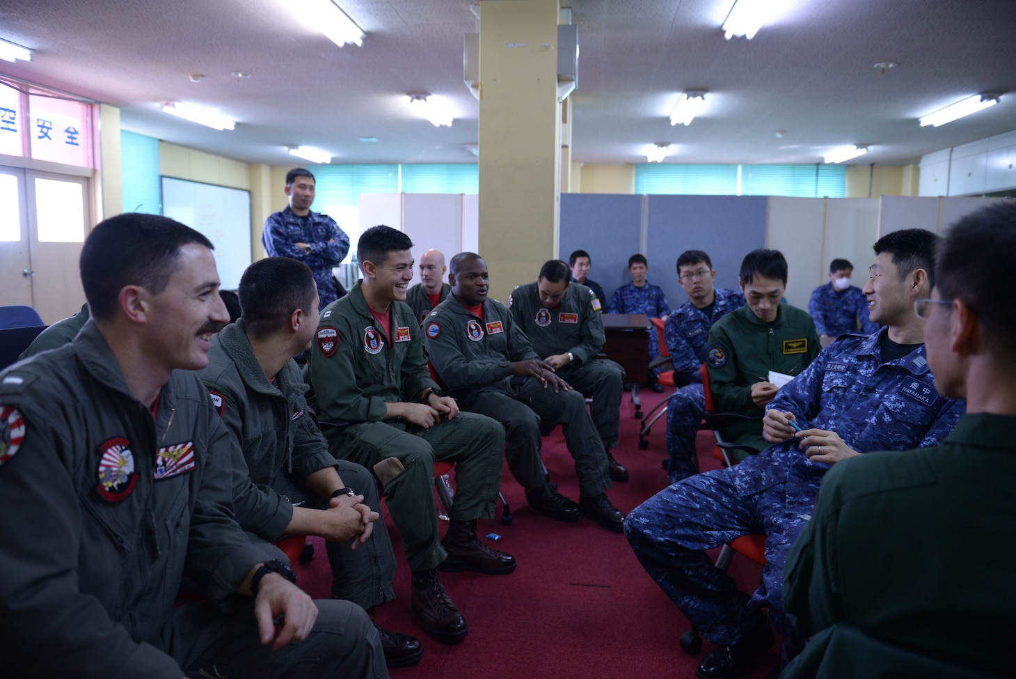 """ATSUGI, Japan (Mar. 14, 2019) — Sailors assigned to the """"War Eagles"""" of Patrol Squadron (VP) 16 meet with the Japan Maritime Self-Defense Force (JMSDF) Sailors assigned to (VP) 3. VP-16 took part in a Trilateral Anti-Submarine Warfare Exercise which included Royal Navy, JMSDF and U.S. assets."""