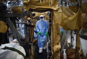 An Airman carries a training dummy into a transportation isolation system during an exercise at Joint Base Charleston, South Carolina, March 5, 2019. Engineered and implemented after the Ebola virus outbreak in 2014, the TIS is an enclosure the Department of Defense can use to safely transport patients with highly contagious diseases. (U.S. Air Force photo by Senior Airman Cody R. Miller)