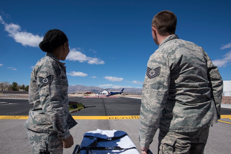 Paramedics with the 99th Medical Group prepare to engage in the Mercy Air exercise on the helipad at the Mike O'Callaghan Military Medical Center, Nellis Air Force Base, March 13, 2019. Mercy Air provides safe, rapid transport by helicopter of critically ill and injured patients. (U.S. Air Force photo by Airman 1st Class Bailee A. Darbasie)