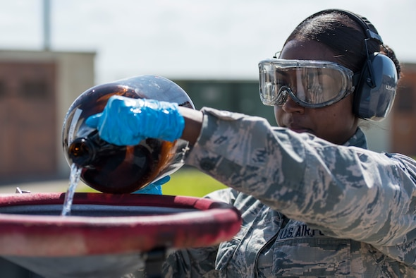 U.S. Air Force Staff Sgt. Akila Mohabir, a 6th Logistics Readiness Squadron fuels laboratory technician, pours excess fuel in a fuel storage tank at MacDill Air Force Base, Fla., March 14, 2019.