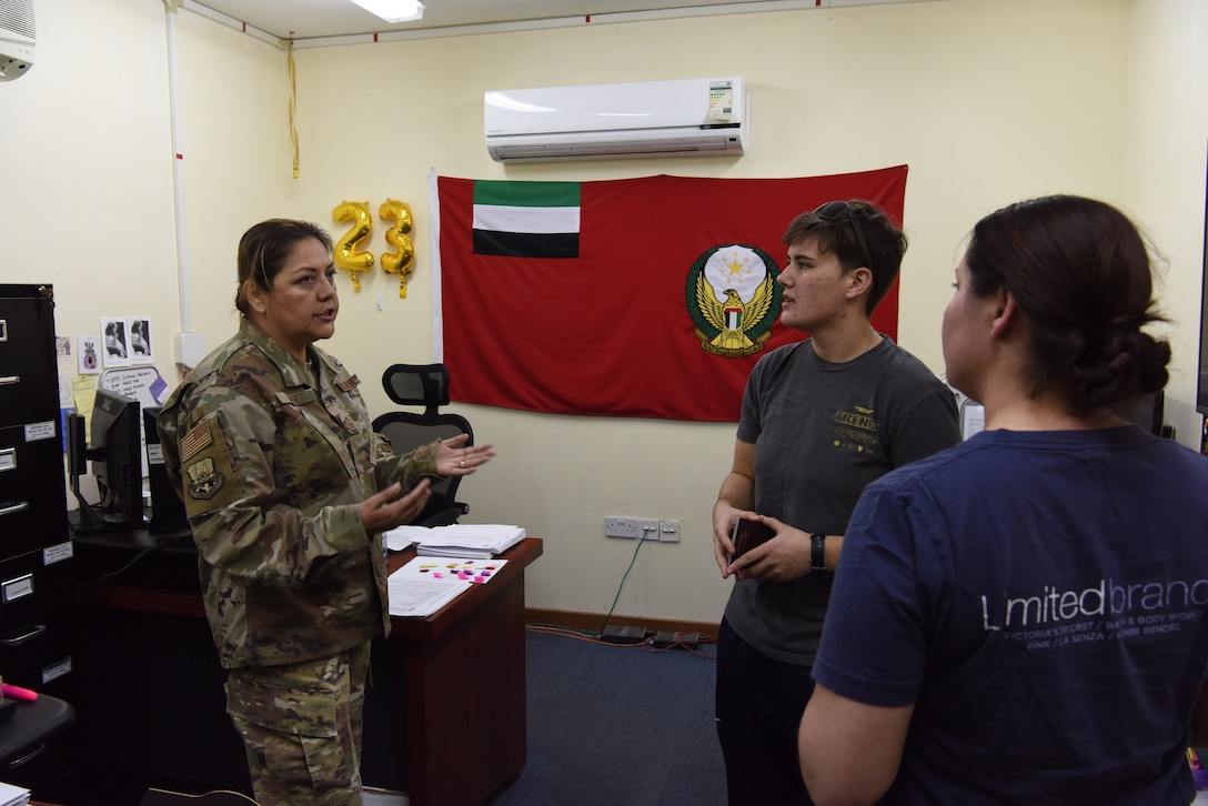 Senior Master Sgt. Margarita Jimenez, 380th Air Expeditionary Wing Host Nation Coordination Office superintendent, answer passport questions from inbound members at Al Dhafra Air Base, United Arab Emirates, Mar. 8, 2019.