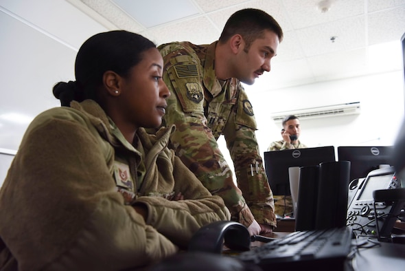 Tech. Sgt. Kathryn Glenn, 380th Expeditionary Logistics Readiness Squadron NCOIC, logistics plans, and Capt. Mark Dellaquila, 380th ELRS Installation Deployment Officer, answers a call about redeployments at Al Dhafra Air Base, United Arab Emirates, Mar. 14, 2019.