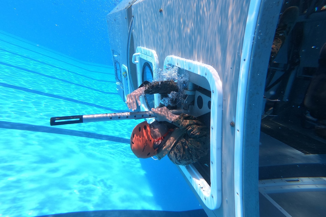 A man swims out of a helicopter window underwater.