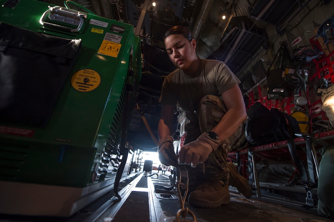 Staff Sgt. Jessica Hakert, 379th Expeditionary Aeromedical Evacuation Squadron (EAES) aeromedical evacuation technician, fastens medical equipment to a C-130 Hercules at Al Udeid Air Base, Qatar, before a recent aeromedical evacuation mission.