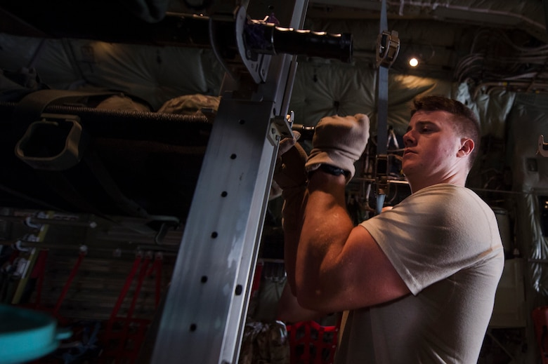 Senior Airman Robert McCabe, left, 379th Expeditionary Aeromedical Evacuation Squadron (EAES) aeromedical evacuation technician, fastens a litter to the inside of a C-130 Hercules at Al Udeid Air Base, Qatar, before a recent aeromedical evacuation mission.