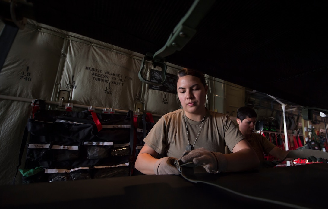 Staff Sgt. Jessica Hakert, 379th Expeditionary Aeromedical Evacuation Squadron (EAES) aeromedical evacuation technician, prepares a litter for transport on a C-130 Hercules at Al Udeid Air Base, Qatar, before a recent aeromedical evacuation mission.