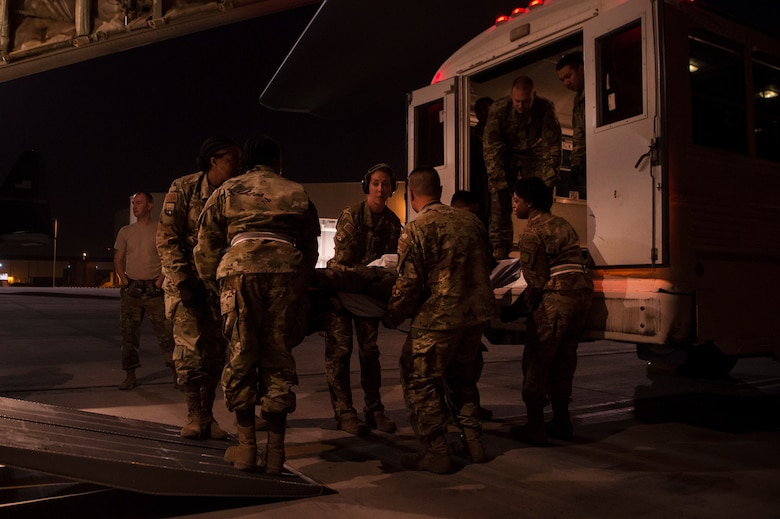 Capt. Aline Putnam, center, 379th Expeditionary Aeromedical Evacuation Squadron (EAES) flight nurse, helps Airmen of the 379th Expeditionary Medical Group's En Route Patient Staging Facility, move a patient for transport at Al Udeid Air Base, Qatar, after a recent aeromedical evacuation mission.