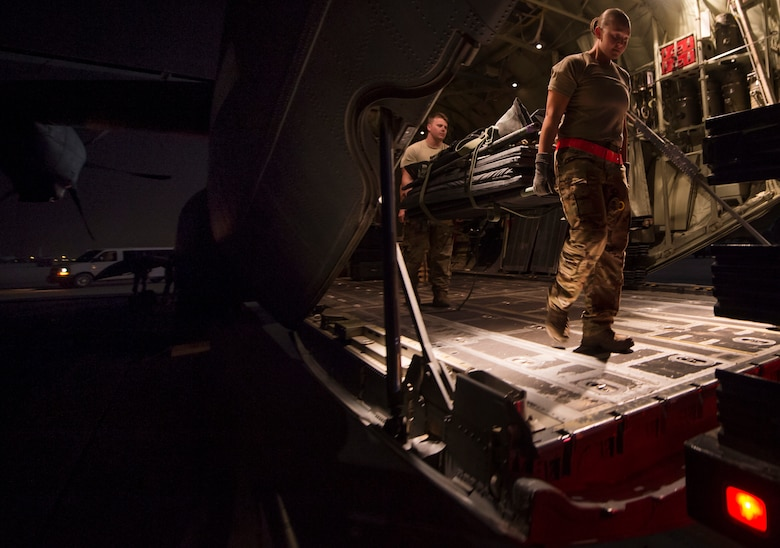 From left, Senior Airman Robert McCabe and Staff Sgt. Lyndsey Glotfelty, 379th Expeditionary Aeromedical Evacuation Squadron (EAES) aeromedical evacuation technicians, move medical equipment onto a truck at Al Udeid Air Base, Qatar, after a recent aeromedical evacuation.