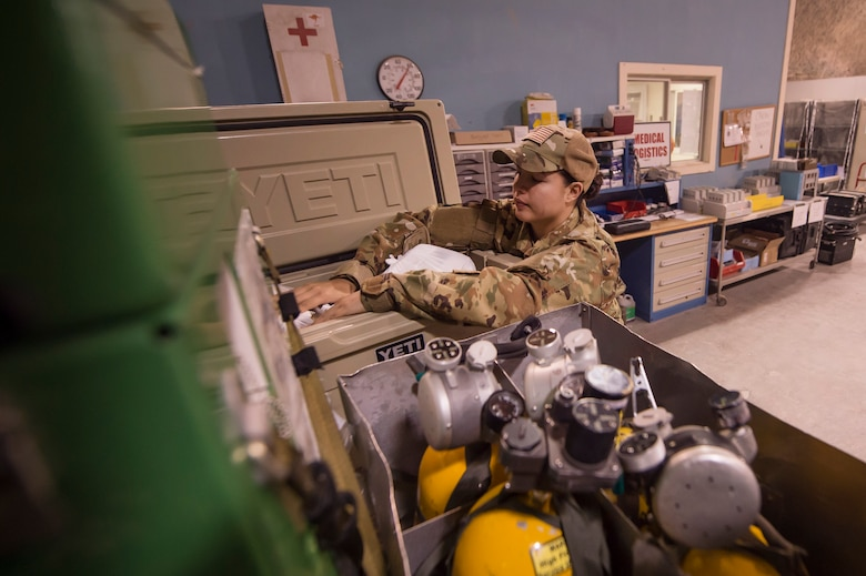 Staff Sgt. Jessica Hakert, 379th Expeditionary Aeromedical Evacuation Squadron (EAES) aeromedical evacuation technician, organizes medical equipment at Al Udeid Air Base, Qatar, before a recent mission.