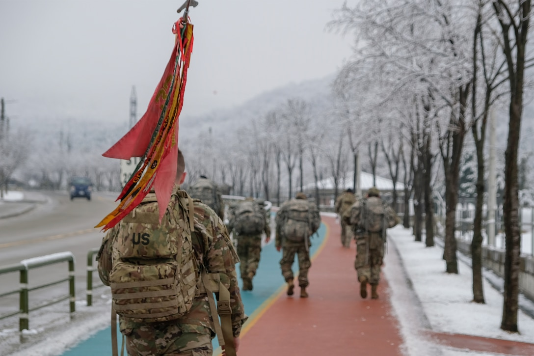 Soldiers march along a pathway with snow on the ground.