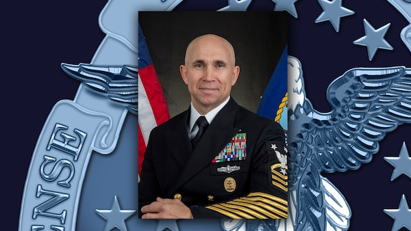 Official photo of Navy Master Chief Petty Officer James Butler against DLA rotator background.