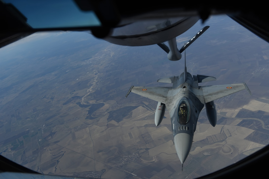A Romanian air force F-16 receives fuel from a KC-135 Stratotanker from RAF Mildenhall, England during training over the skies of Romania, March 11, 2019. The training was an example of U.S. and NATO allies sharing a commitment to promote peace and stability through developing their relationship and communication process. (U.S. Air Force photo by Airman 1st Class Brandon Esau)