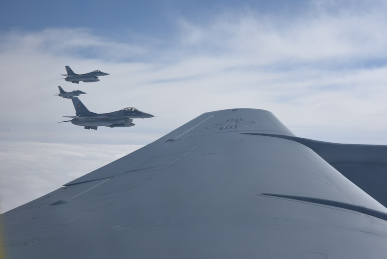 Romania air force F-16s fly in formation with a KC-135 Stratotanker from RAF Mildenhall, England during air refueling training over the skies of Romania March 12, 2019. The training was an example of U.S. and NATO allies sharing a commitment to promote peace and stability through developing their relationship and communication process. (U.S. Air Force photo by Airman 1st Class Brandon Esau)