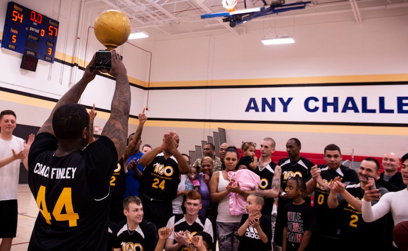 The coach of team U.S. Army Central Command (ARCENT) holds up a trophy following the completion of an intramural basketball championship game at Shaw Air Force Base, S.C., March 14, 2019.