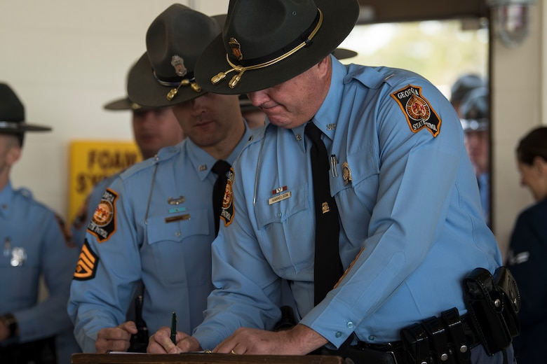 A Georgia State Patrolman signs in before the Celebration of Life ceremony honoring the late Mr. W. Parker Greene, March 14, 2019, at Moody Air Force Base, Ga. Greene, a steadfast Air Force advocate and one of the most influential military civic leaders passed away Dec. 18, 2018. (U.S. Air Force Photo by Senior Airman Janiqua P. Robinson)