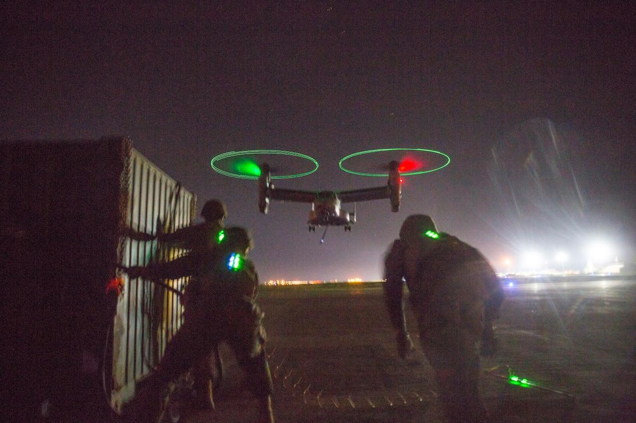 Marines run toward hovering aircraft