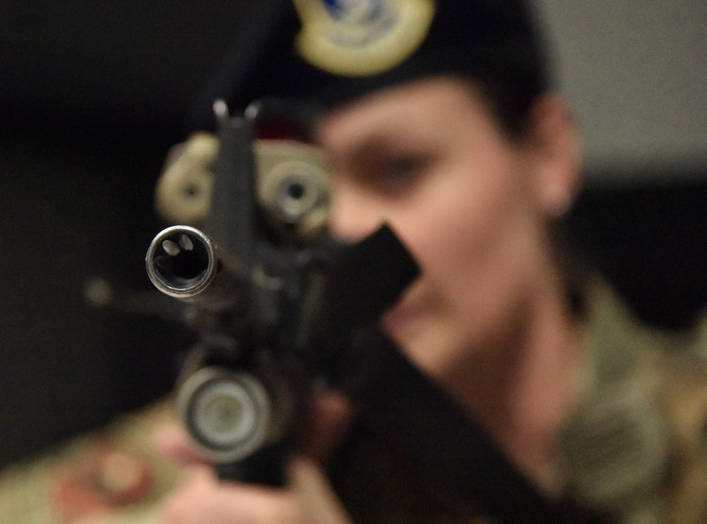 """U.S. Air Force Staff Sgt. Emily Arceneaux, 81st Security Forces Squadron police services NCO in charge, aims her weapon towards the room where the """"shooter"""" has barricaded himself during an 81st SFS active shooter training demonstration at Keesler Air Force Base, Mississippi, March 14, 2019. The scenario included a disgruntled Airman with marital problems and a pending administrative discharge who ran the entry gate which then escalated to an active shooter situation. Leadership attended the event, which is one of several in recognition of the Year Of The Defender, to observe what steps Keesler Defenders take during a high intensity situation, such as an active shooter, in preparation for real-world situations. (U.S. Air Force photo by Kemberly Groue)"""