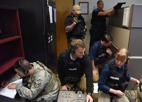 """Members of the 81st Security Forces Squadron hostage negotiation team prepare to negotiate with the """"shooter"""" during an 81st SFS active shooter training demonstration at Keesler Air Force Base, Mississippi, March 14, 2019. The scenario included a disgruntled Airman with marital problems and a pending administrative discharge who ran the entry gate which then escalated to an active shooter situation. Leadership attended the event, which is one of several in recognition of the Year Of The Defender, to observe what steps Keesler defenders take during a high intensity situation, such as an active shooter, in preparation for real-world situations. U.S. Air Force Staff Sgt. Kevin Rozas, 81st Security Forces Squadron office of special investigations joint drug enforcement team leader, said that maintaining readiness is the number pone priority for the 81st SFS and it is always good to train in different scenarios because every situation is different so expectations vary, but the training is constant. (U.S. Air Force photo by Kemberly Groue)"""