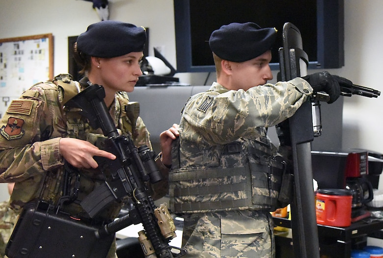 U.S. Air Force Staff Sgts. Emily Arceneaux, 81st Security Forces Squadron police services NCO in charge, and James Vaughan, IV, 81st SFS unit trainer, prepares to drop a phone box to be used for negotiations during an 81st SFS active shooter training demonstration at Keesler Air Force Base, Mississippi, March 14, 2019. The scenario included a disgruntled Airman with marital problems and a pending administrative discharge who ran the entry gate which then escalated to an active shooter situation. Leadership attended the event, which is one of several in recognition of the Year Of The Defender, to observe what steps Keesler defenders take during a high intensity situation, such as an active shooter, in preparation for real-world situations. (U.S. Air Force photo by Kemberly Groue)