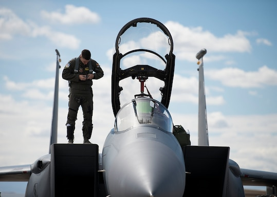 U.S. Air Force 1st Lt. Mathew Clutts, a Weapons System Officer (WSO) on an F-15E Strike Eagle fighter jet assigned to the 336th Fighter squadron, buckles up his harness while standing on top of an F-15E at Nellis Air Force Base, Nev., March 12, 2019. A WSO's job is to select targets and navigate with the aid of a moving map display, produced by an AlliedSignal remote film strip reader.