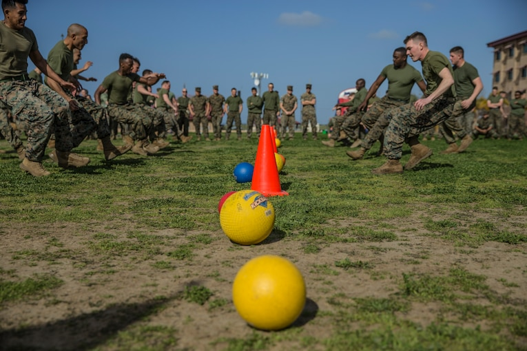 A group of Marines run towards a line of dodge balls.