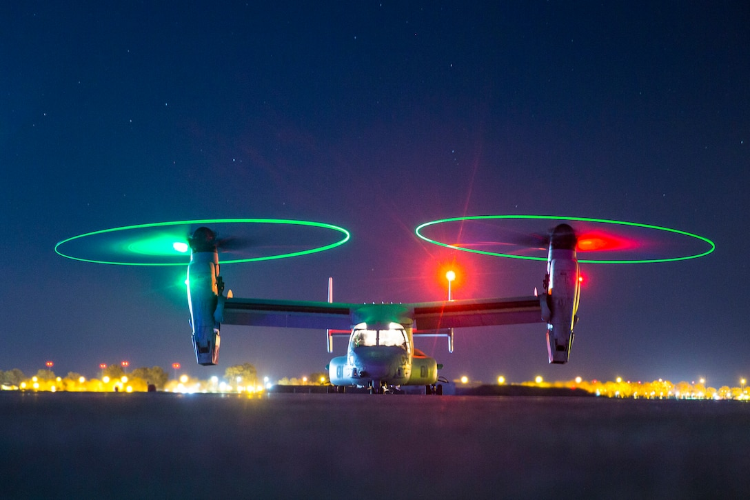 A helicopter parked with it's lights on at night.