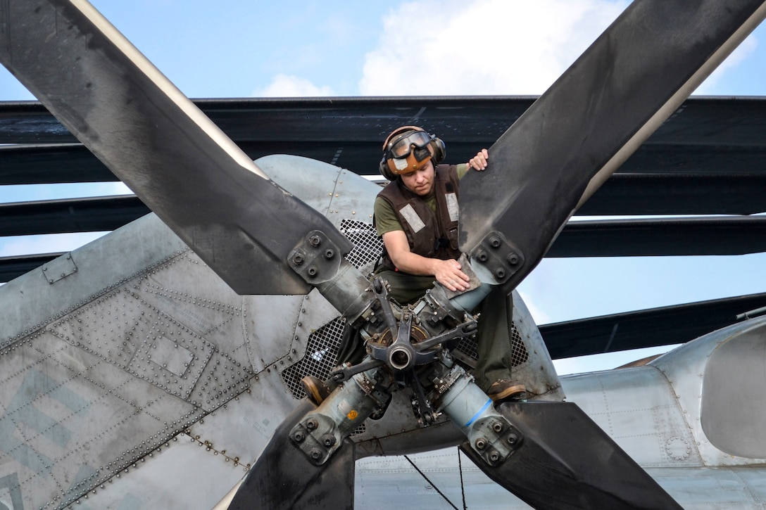 A Marine wipes down a propeller.
