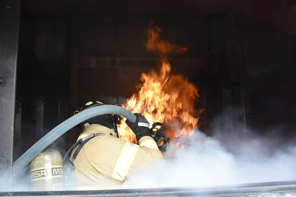 """Arnold Air Force Base firefighter Marvin Greeson battles a blaze in the """"living room"""" of the simulator recently used by the Arnold AFB Fire and Emergency Services. The simulator replicates flames, smoke and heat firefighters typically encounter while responding to a structure fire. (U.S. Air Force photo by Bradley Hicks)"""