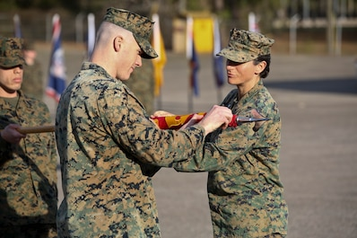 Lt. Col. Kate Murray and Capt. Kevin Buonomo handle the company guidon during Combat Logistics Company 23's realignment ceremony aboard Marine Corps Air Station Beaufort, March 15. Buono is the Company Commander of CLC-23 and Murray is the Commanding Officer of 2nd Maintenance Battalion.