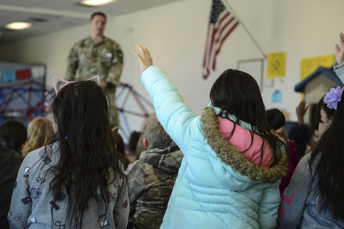 Staff Sgt. Brenden David, 377th Security Forces Squadron Military Working Dog trainer supervisor, answers the questions of students from the Sandoval Academy of Bilingual Education in Rio Rancho, N.M., March 15, 2019. During the MWD demonstration, the team showed the students what and how the dog assists his handler. (U.S. Air Force photo by Staff Sgt. Kimberly Nagle)